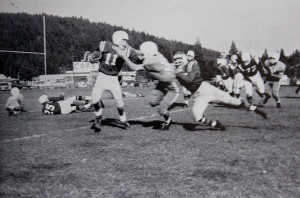 QB Butch Smith gives a Carson Senator a stiff arm as he breaks outside