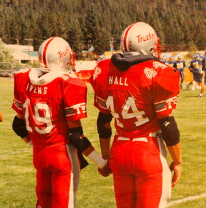 "(19) Josh Ivens and (44) Jevon Hall await the coin toss. 1991 was the first year the captains joined hands as a sign of ""Family"" walking out to the coin toss."